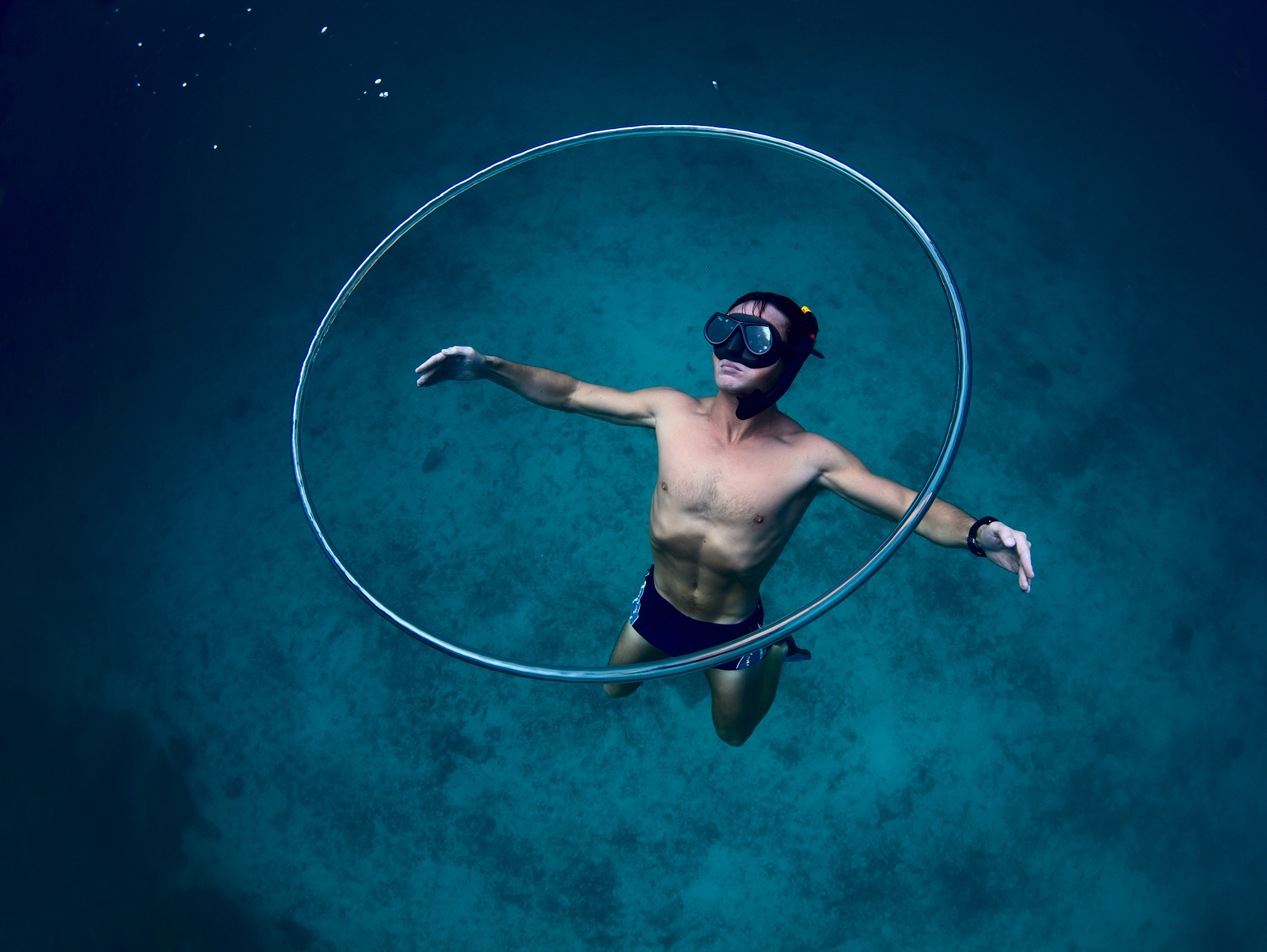 Young freediver making huge ring bubbles underwater and gliding near it